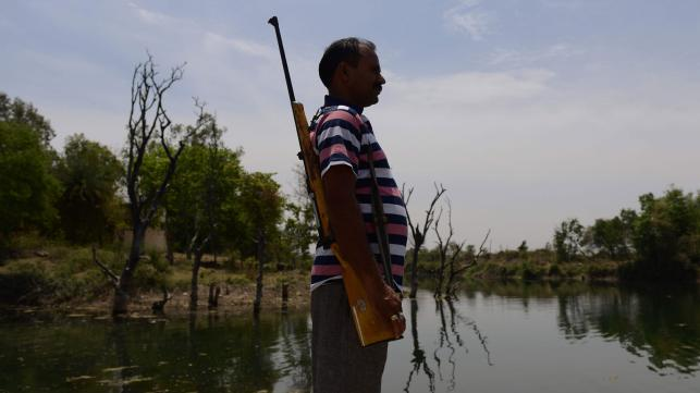 An armed guard protects the water canal from local exploitation