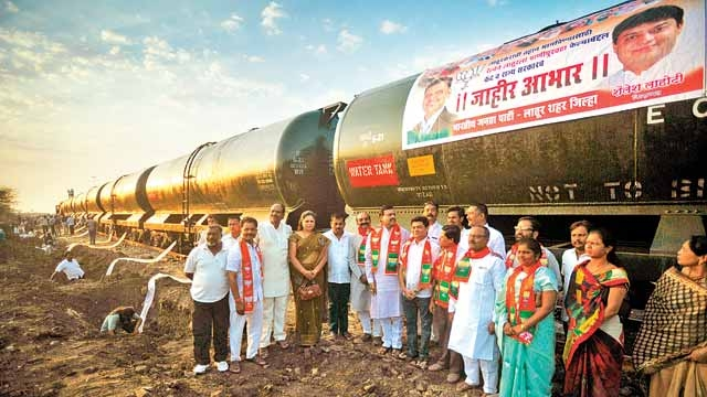 BJP party workers pose for a picture in front of the first water train in Latur, Maharashtra.