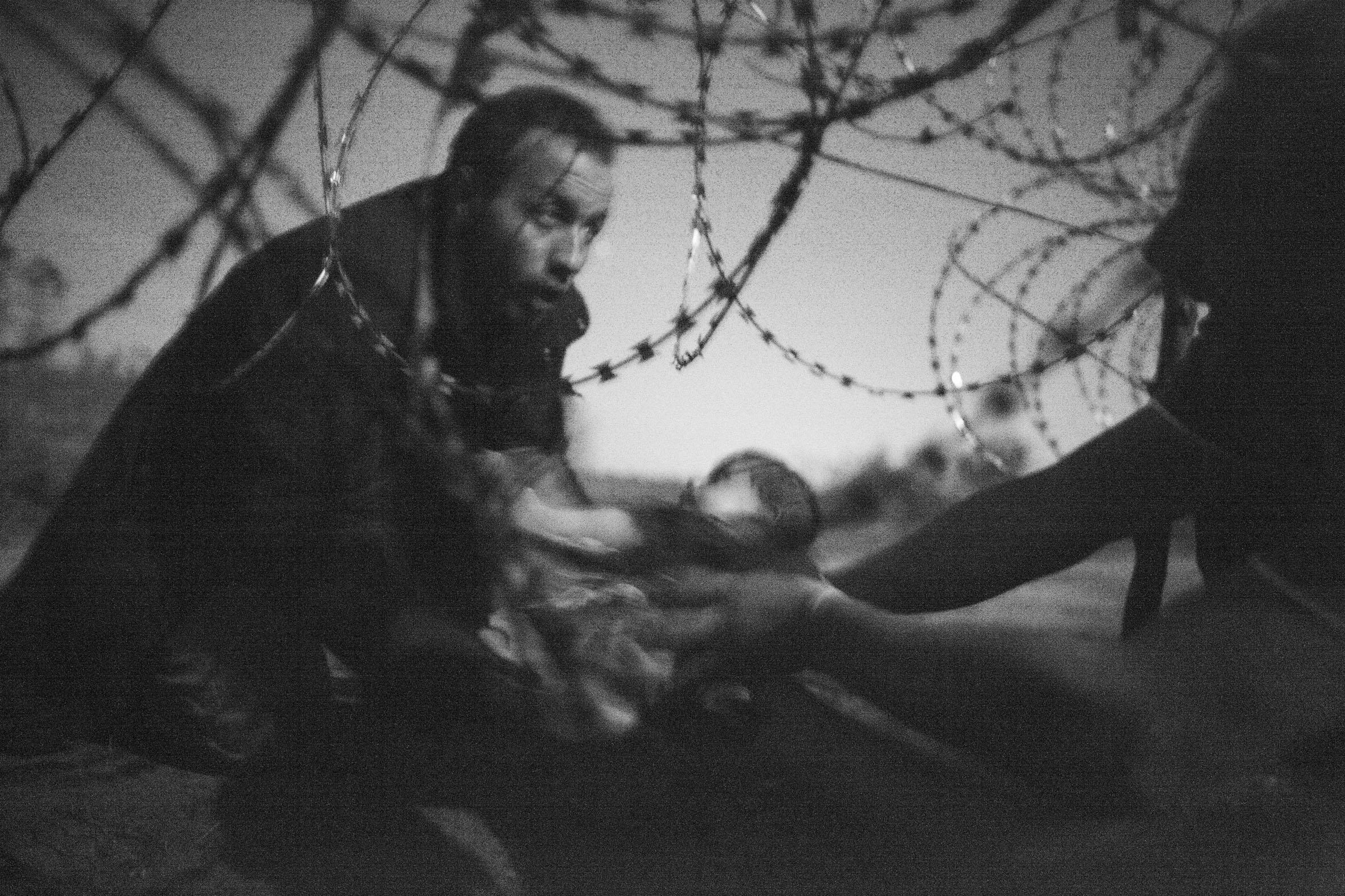 World Press Photo Of the Year by Warren Richardson. Titled, Hope For A New Life, it depicts a baby being handed through a hole in a razor wire barrier, to a Syrian refugee who has already crossed the borderfrom Serbia into Hungary, near Röszke.