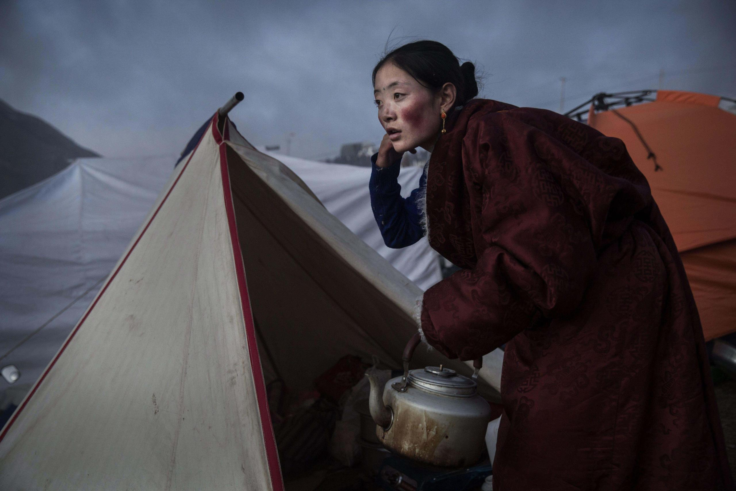 From the photo series Bliss Dharma Assembly by Kevin Frayer. A Tibetan Buddhist nomad woman prepares tea at dusk, following a chanting session.